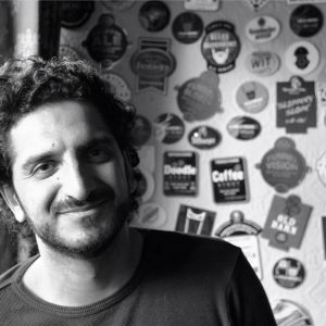 Headshot of Timon Singh. A black and white image of a smiling man in a dark top with short curly hair in front of a wall covered what appear to be beer mats