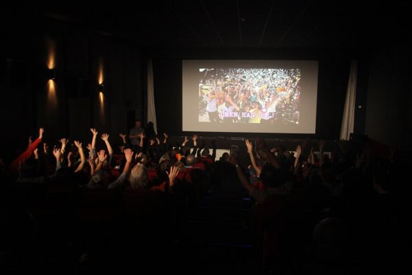 Photograph of a cinema screening, where all the audience have raised their arms