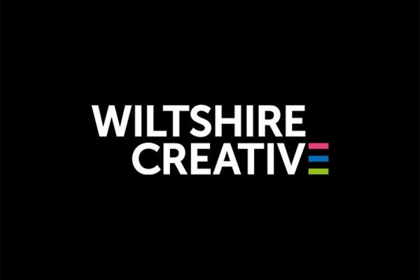 Graphic text image of Wiltshire Creative. White writing on black, and the 'E' in creative is comprised of colourful horizontal stripes