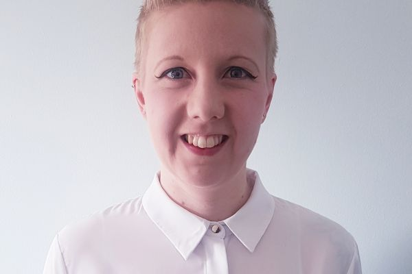 head shot of talent exec Alix Taylor. She stands centrally in a white room wearing a white shirt. visible from shoulders up she is smiling, white with short blond hair.