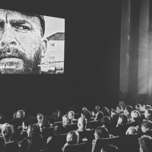 A black and white image of people sat watching a film