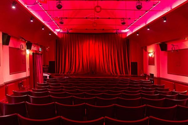 Inside a cinema auditorium, plush space with red lighting, chairs, and curtain