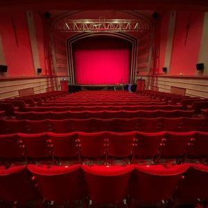 An empty cinema, shot taken as though seated at the back looking over rows of chairs to a red screen. All seats and walls are red giving warm glow to the low lighting