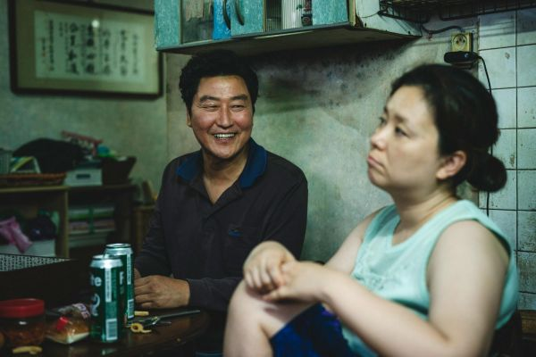 film still of Parasite. A smiling man looks at a woman to his right around a table with beers on