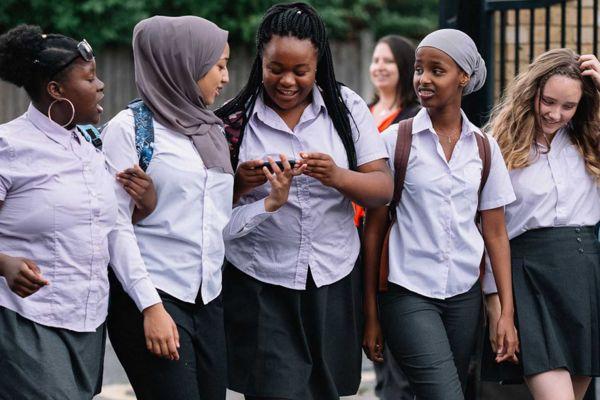 Films till from rocks. Five girls in school uniform walk, talk and link arms
