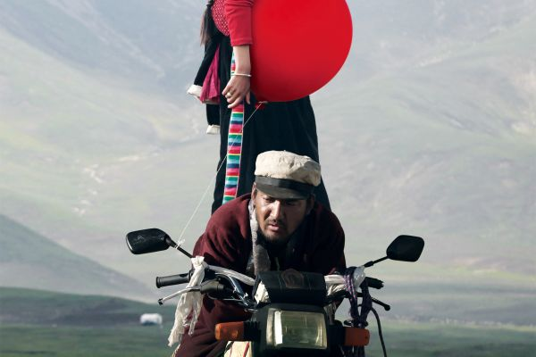 Movie poster for 'Ballon'. Portrait image of a man ridging a motorbike with a woman standing on back holding a red balloon