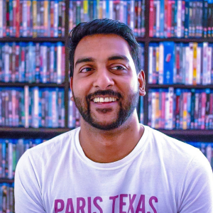 Headshot of Community Manager Neil Ramjee. Neil, a man of South Asian heritage, smiles in a white t-shirt in fornt of an impressive DVD shelf