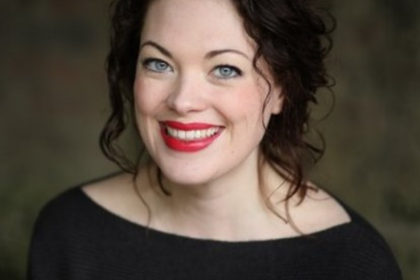 Headshot of Jess Jones. a white woman with dark curly hair. red lipstick and a dark top, she is smiling widely