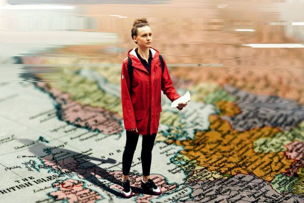 A woman in a red coat stands looking bewildered holding a piece of paper. We look at her standing looking comically large stood on a printed map of the world. However, her posturing and the angle looking down makes her look small.