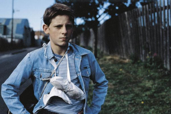 Film Still from Billy Elliot. A boy with ballet shoes around his neck looks discontent