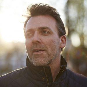 Headshot of Paul Thomas, outside and smiling