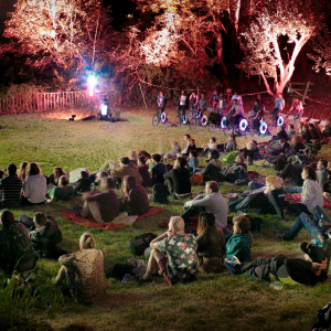 A brightly lit audience sits on an inclining hill, looking towards a screen out of shot. Colourful lighting illuminates trees, whilst people ride neon lit bikes that power a generator
