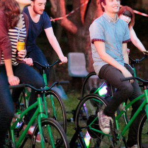 A group of people cycle on stationary green bikes. They talk and drink beer, their cycling bowering a nearby generator.