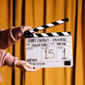someone in a light pink jumper holds a clapper board in front of a mustard curtain