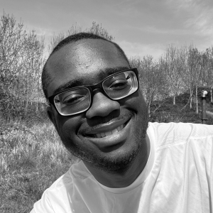 black and white image of Daniel Granville smiling, with short, nearly shaved head and glasses