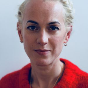 Headshot of Alison Hargeaves. Alison has short blonde hair and a red jumper
