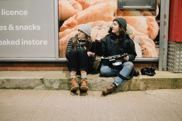 Two people sat on the curb, one holding a monitor. they both look towards their left. it appears to be a service station at night, they look cosy and in control.