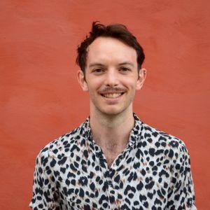 Headshot of Matthew Short. Matthew smiles in a patterned top against a orange wall