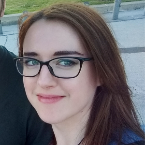 Headshot of a smiling Kayleigh Gibbons with long straight brown hair and glasses