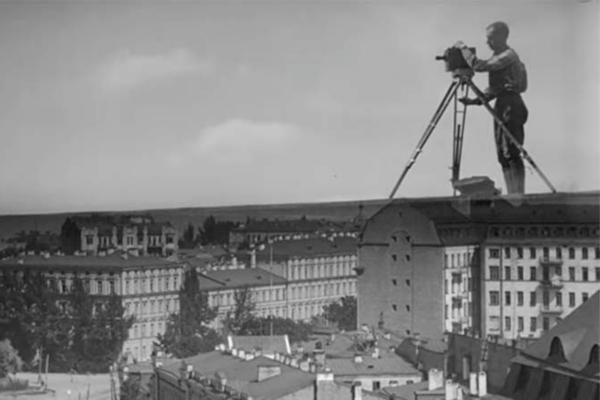 black and white film still. a larger than life person operates a camera, stood as though on the roofs of many houses
