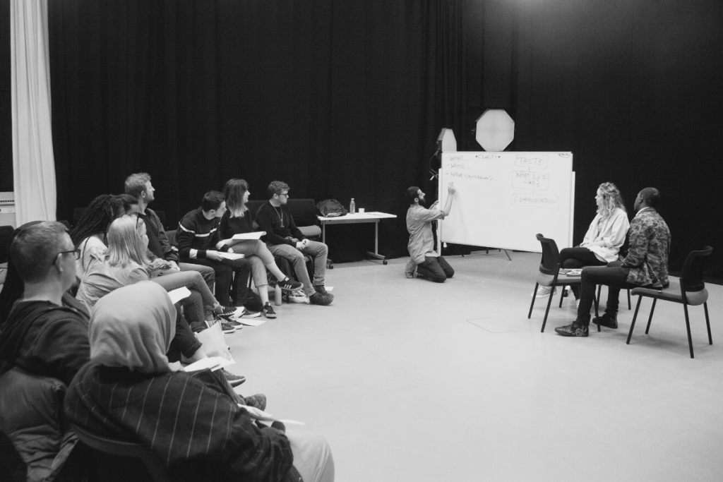 black and white image of a man teaching a workshop. a group of people sit in a curved semi circele, as one draws on a whiteboard