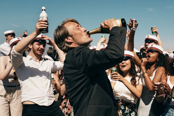 central image of Mads Mikkelsen drinking a bottle of champagne with it in the air - a crowd dressed as sailors cheer him on. the sky is blue, it appears a fun sunny day