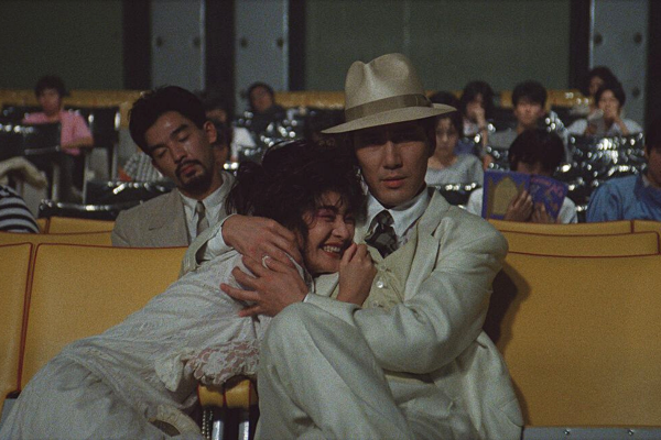 a man and a woman dressed in white sit in a cinema on a yellow seat. they embrace tightly. the crowd is bored behind