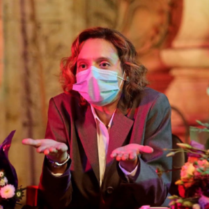 a woman wearing a surgical mask and grey suit shrugs exaggeratedly.