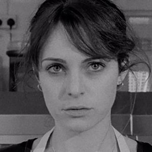 black and white image of a woman staring at the camera, she has a concerned look and dark straight hair. image is a still from the short film HARD, CRACKED THE WIND.