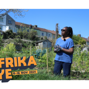 still from Africa eye short film woman stands in a Bristol allotment on a blue skied day.