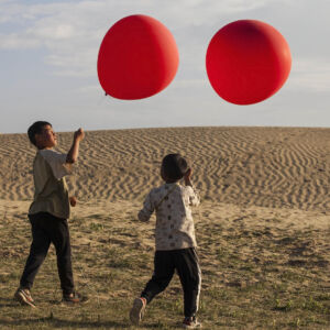 film still. a desert with two children running across, holding two large red balloons